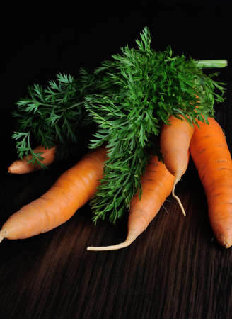 bundle of raw carrots on the table dark background