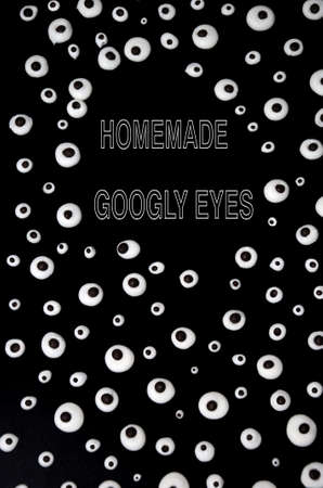 Many from homemade googly eyes meringue with chocolate look at each other against a black background on Halloween