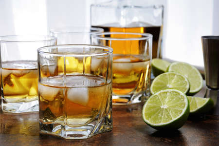 Photo pour Alcohol cocktail with brandy, whiskey or rum with Ginger Ale, lime and ice in glasses - image libre de droit