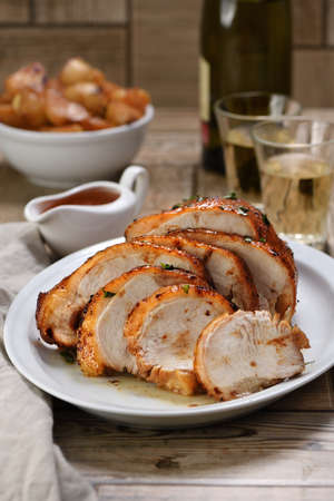 Photo pour Sliced into slices baked turkey breast   at the dinner table - image libre de droit
