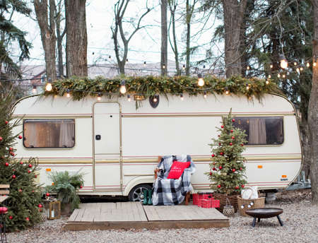 Photo pour Vintage old travel trailer with Christmas decorations, Christmas tree, chair and Christmas lights. Cozy home, camping before Christmas holidays. - image libre de droit
