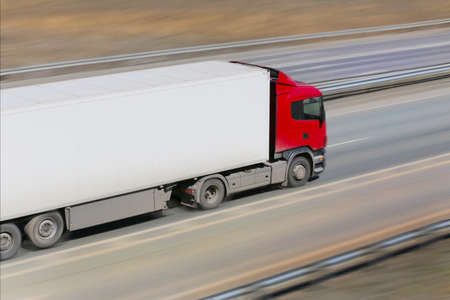 Foto de trailer with red awning moves at high speed on the highway - Imagen libre de derechos
