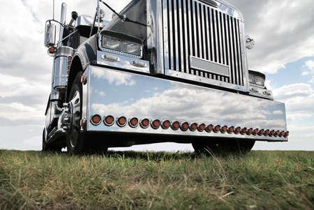 Foto de big black brilliant American truck in field - Imagen libre de derechos