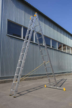aluminum step-ladder at metal wall of warehouse