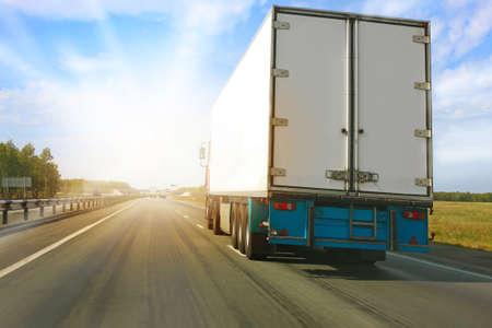 Foto de big truck goes on the highway to sunrise - Imagen libre de derechos