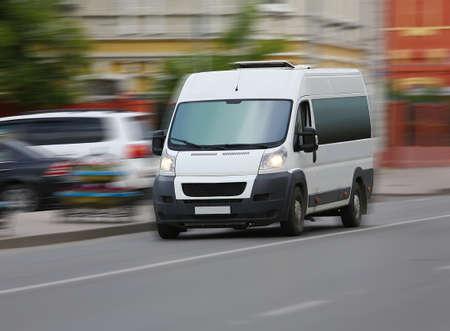 Photo pour white minibus goes on the city street - image libre de droit