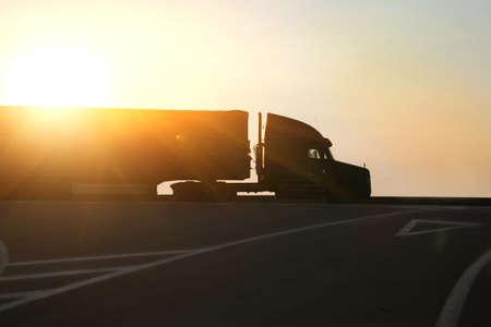 Foto de truck goes on highway in evening on sunset - Imagen libre de derechos