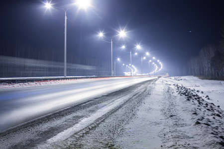 winter highway at night shined with lamps