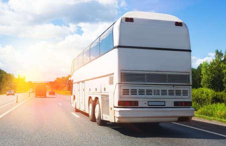 Photo pour tourist bus goes on highway in beams of sun - image libre de droit