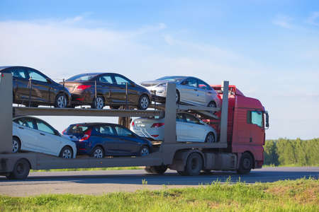 Photo for transportation of car on semi-trailer on country highway - Royalty Free Image