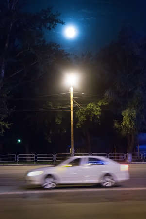 night landscape with moon and traveling car illuminated by flashlight