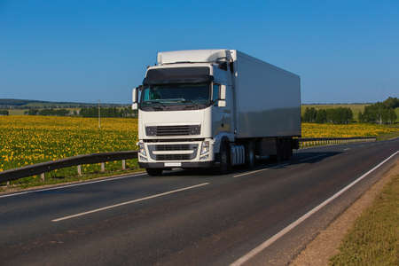 big white truck moves on highway along field of sunflowers