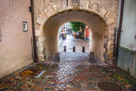 old cobbled street and house with arch in the center of Riga, Latvia.