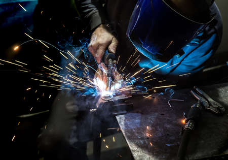 Photo for welder in mask welds metal details - Royalty Free Image
