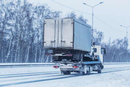 Photo pour Car tow truck transports a broken truck along a winter road - image libre de droit