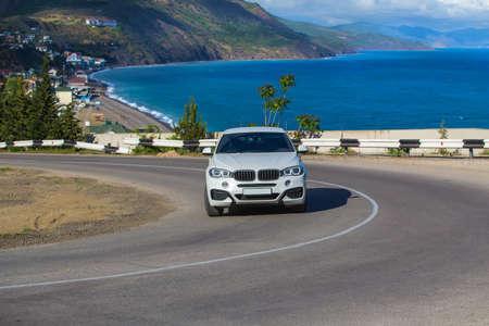 Photo pour Car Moves along a winding road along the sea shore. - image libre de droit
