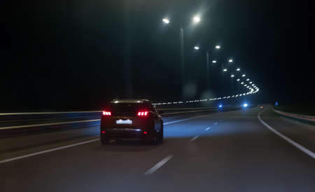 Photo pour Car moves at high speed on a suburban highway at night. - image libre de droit