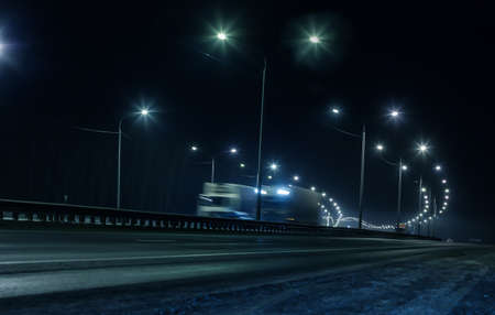 Photo pour Truck traffic on a winter highway at night - image libre de droit