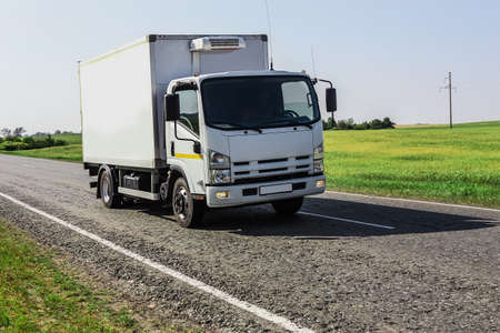 Photo for Truck is driving along a country road along a field - Royalty Free Image
