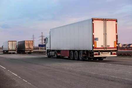 Photo for Trucks semi-trailers moving on a suburban highway - Royalty Free Image