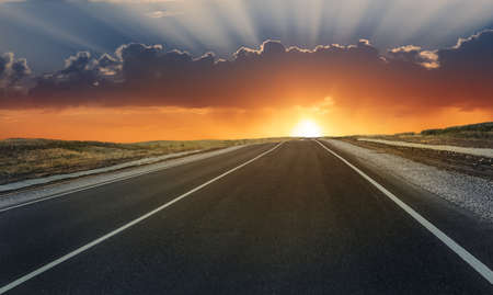 Photo for Road lit by the sun at sunset in the cloudy sky - Royalty Free Image