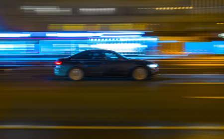 Photo pour Black car drives along a city street at night. Blurry motion. - image libre de droit