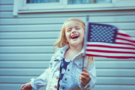 Cute little girl with long curly blond hair laughing and waving american flag. Independence Day, Flag Day concept. Vintage and retro colors.