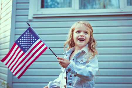 Pretty little girl with long curly blond hair smiling and waving american flag. Independence Day, Flag Day concept. Vintage and retro colors.