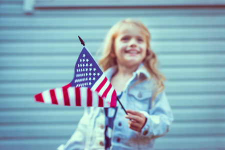 Flying american flag in little girl's hand. Selective focus, blurred background. Independence Day, Flag Day concept. Vintage and retro colors. Instagram filters