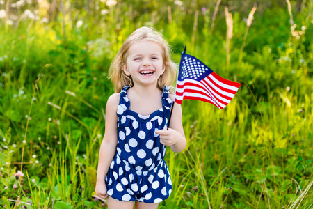 Photo pour Beautiful little girl with long curly blond hair with american flag in her hand laughing on sunny day in summer park. Independence Day Flag Day concept - image libre de droit