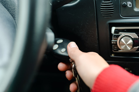 Female driver hand inserting car key and starting engine. Closeup