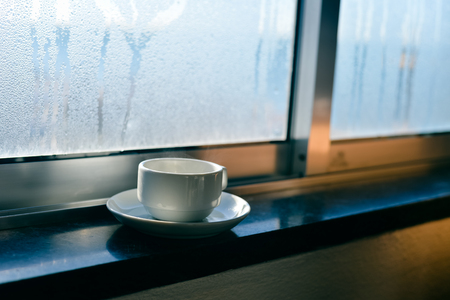 Coffee cup on fogged or frozen window background. drawn symbol sign