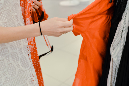 Closeup on hands of a woman holding choosing clothes on shopping background. Modern consumerism lifestyle