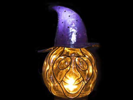 Pumpkin with a magic purple hat with a candle on a black background