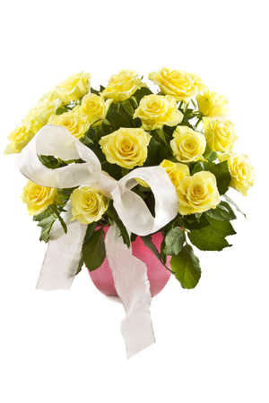 Yellow roses with decorative knot in a pink vase isolated