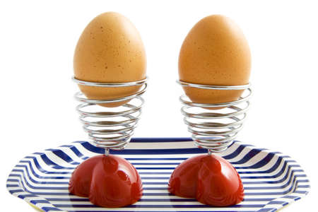 Two eggs in egg cups on a tray isolated over white