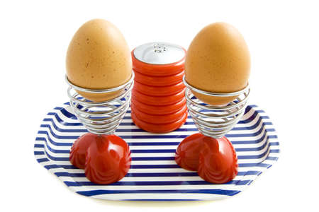Two eggs in eggcups on a tray with saltshaker isolated over white