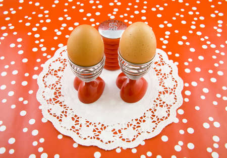 two eggs in eggcups with saltshaker on a speckles background