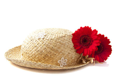 Straw hat with two red gerbera's over white