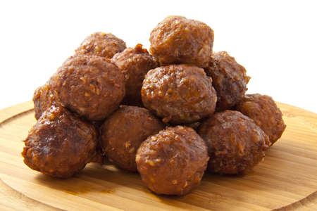 Meatballs on a wooden plate on a white background