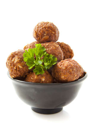 Meat balls in a black bowl isolated over white