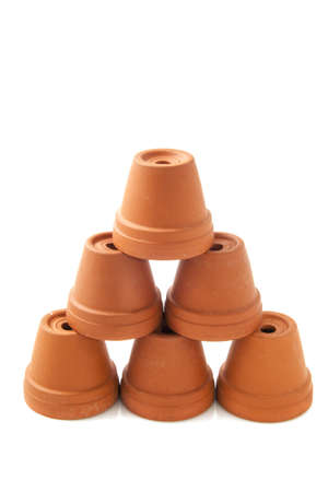 Ceramic orange flowerpots on a pile isolated over white