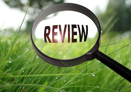 Magnifying glass with the word review on grass background. Selective focus