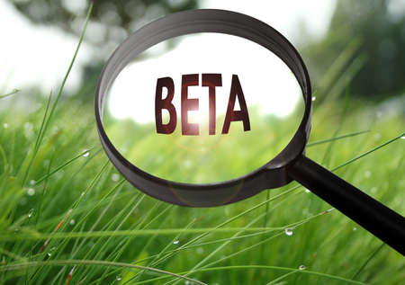 Magnifying glass with the word beta on grass background. Selective focus