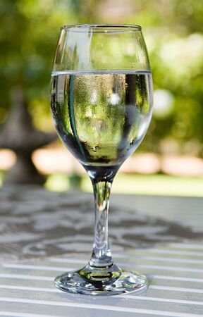 Glass of cold water on garden table in hot summer