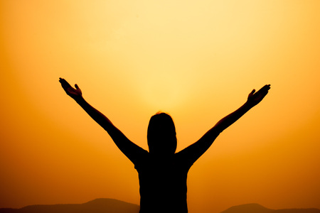 Photo pour Silhouette of woman on a summit with upraised arms on the top mountain with the sunset, Praise for GOD. - image libre de droit