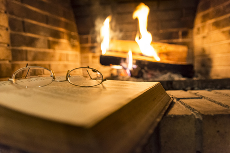 Photo for open book with glasses on it beside fireplace - Royalty Free Image