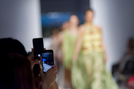 Foto per people from audience filming the fashion show with mobile phone - Immagine Royalty Free