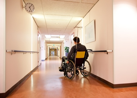 man in wheel chair in empty hospital corridor