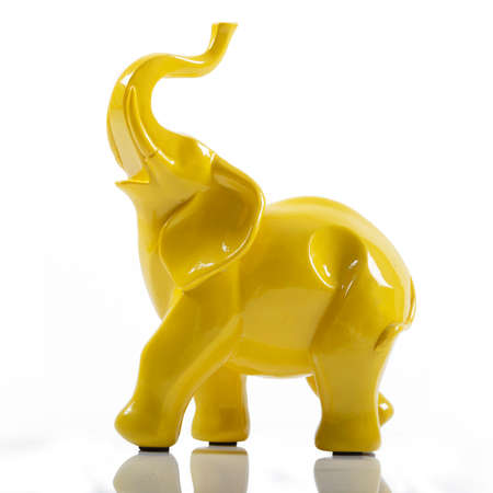 Photo for Yellow Ceramic Porcelain Elephant on White with Reflection - Royalty Free Image